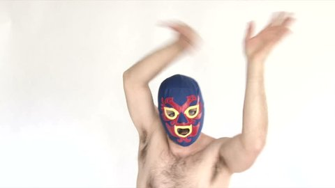 Model released man in studio wearing blue lucha libre mask showing off ridiculous skills.