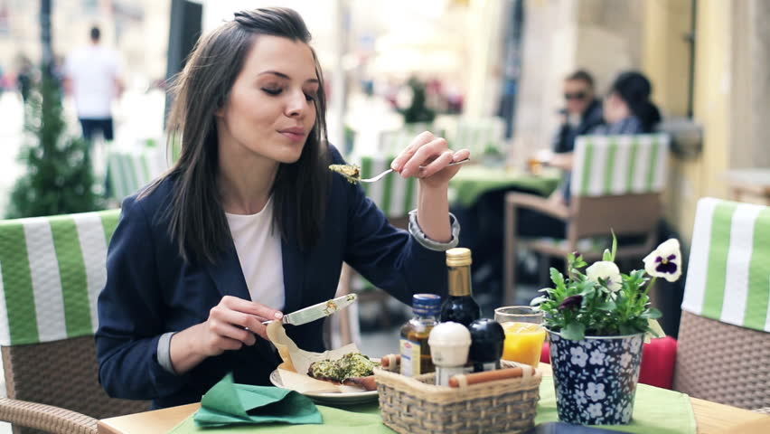 Young businesswoman eating lunch in outdoor restaurant