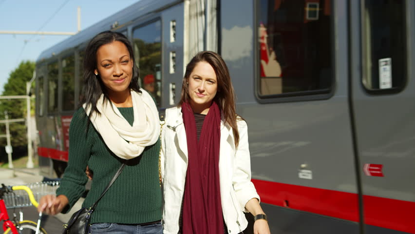 Two girl friends hug and smile at the camera as a tram passes behind them