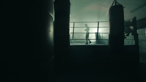 Male Boxer enters jogging into the ring and prepares for the fight