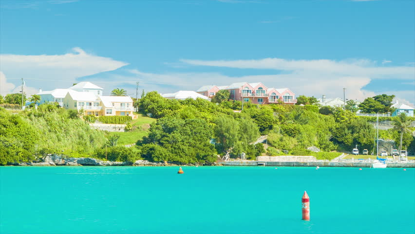 Onboard a Ferry, Sailing Through Bermuda's St. George's Harbor, Featuring Luxury Buildings and Yachts Amonst Lush Greenery and Tropical Turquoise Colored Water on a Sunny Day.