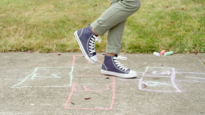 Girl in sneakers jumps down a hopscotch court