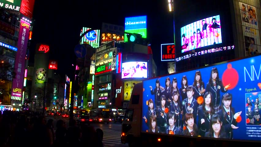 TOKYO, JAPAN - MARCH 24, 2014: Large crowds of pedestrians, commuters, and shoppers cross the famous Shibuya intersection at night on March 24, 2014, in Tokyo, Japan.