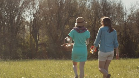 2 Girls Look For A Spot To Have A Picnic In A Field, On A Beautiful Spring Day