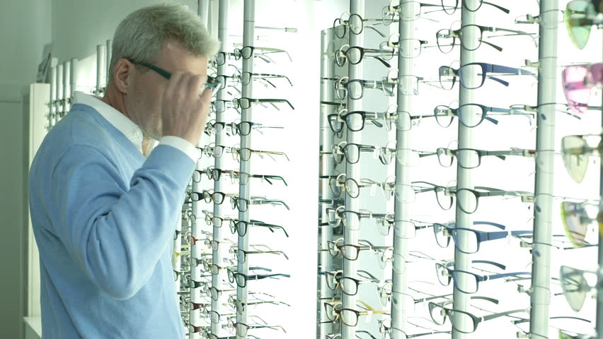 Male customer browses Optician shop and selects glasses to try on | Shutterstock HD Video #6173066