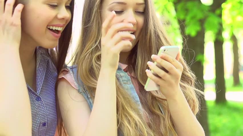 Outdoor portrait of teen friends taking photos with a smartphone. Two  Teenager girlfriends having fun in a park. Teenage Girls making self  portrait. Selfie.