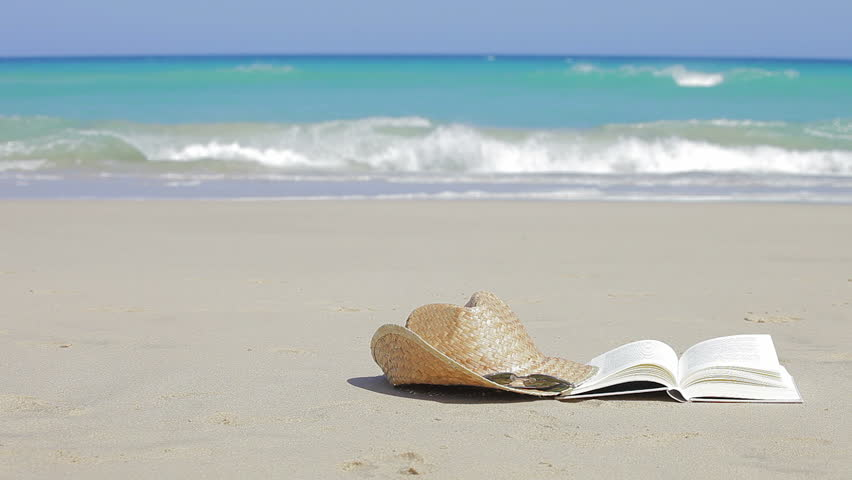 Book, sunglasses and straw hats on the beach. Relax concept (copy space)