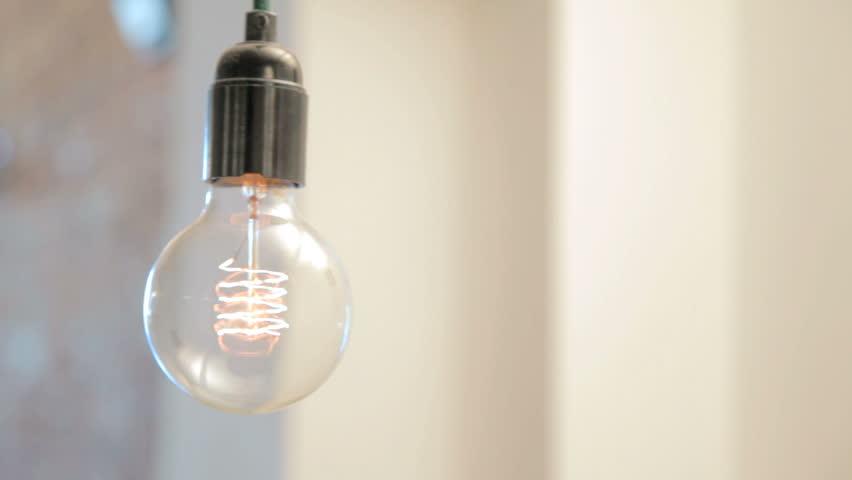 Lightbulb swinging against a bright blurry background | Shutterstock HD Video #6220538