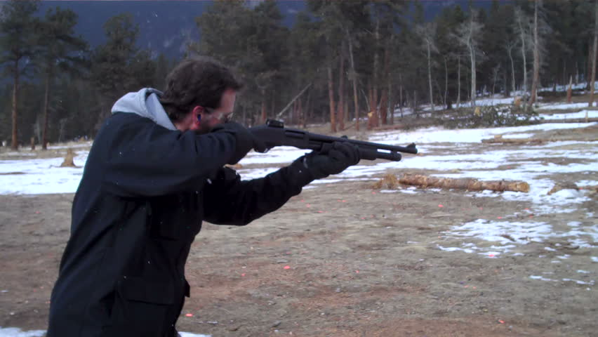 young male firing shotgun