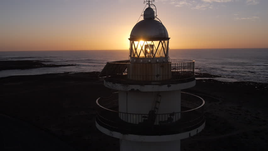 AERIAL: Large lighthouse at sunset