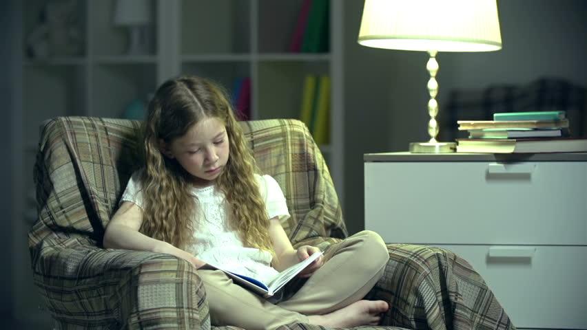 Handheld shot of girl in nursery reading a book with her legs crossed