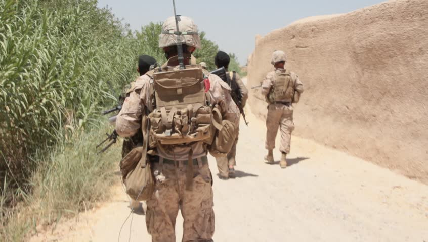 Back of US Marines and Afghan military as they walk on patrol