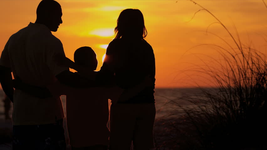 african american family vacation watching sunset young family in silhouette standing on beach quietly watching beautiful sunset shot on red epic stock