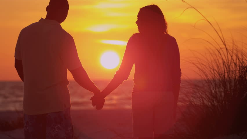 Loving Couple Holding Hands Beach Vacation Sunset - Young ethnic couple holding hands watching sunset on beach vacation shot on RED EPIC