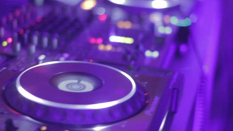 Dj's hands playing mix on sound board, platter spinning. Closeup of professional deejay equipment. Man performing for happy young people moving to music on dance floor at party. Nightclub atmosphere