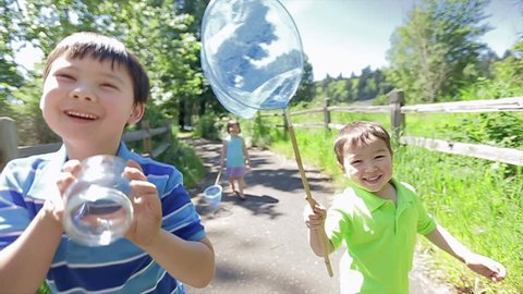 Little Boy Holds Up A Bug Jar And His Younger Brother Holds Up A Butterfly Net. Asian family playing outdoors.