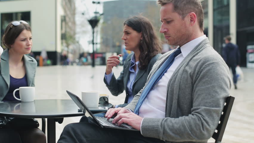 Businesspeople sitting in street cafe, steadycam shot