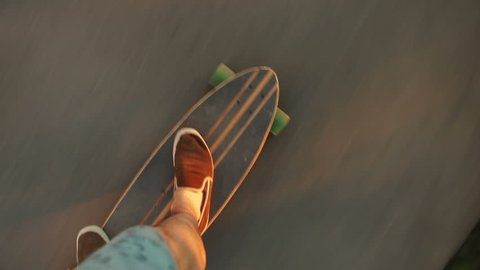 Shot on a longboard from the perspective of the longboard rider (pov). Driving on the asphalt.