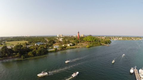 Aerial of a busy Inlet at sunset with the Jupiter Florida Lighthouse.