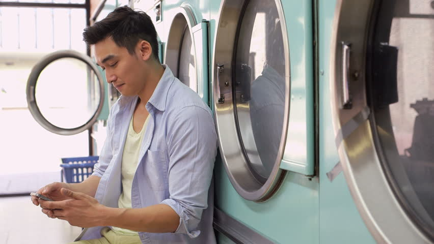A Young Man uses his smartphone whilst waiting for his Laundry