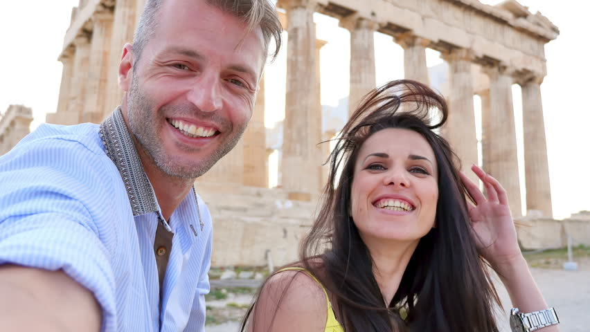 Beautiful couple takes a selfie with the Acropolis in the background.
