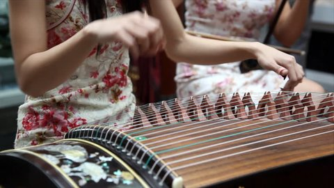 Chinese traditional musician playing chinese guzheng.Guzheng, also called zheng or Chinese plucked zither,is a plucked half-tube zither with movable bridges and strings