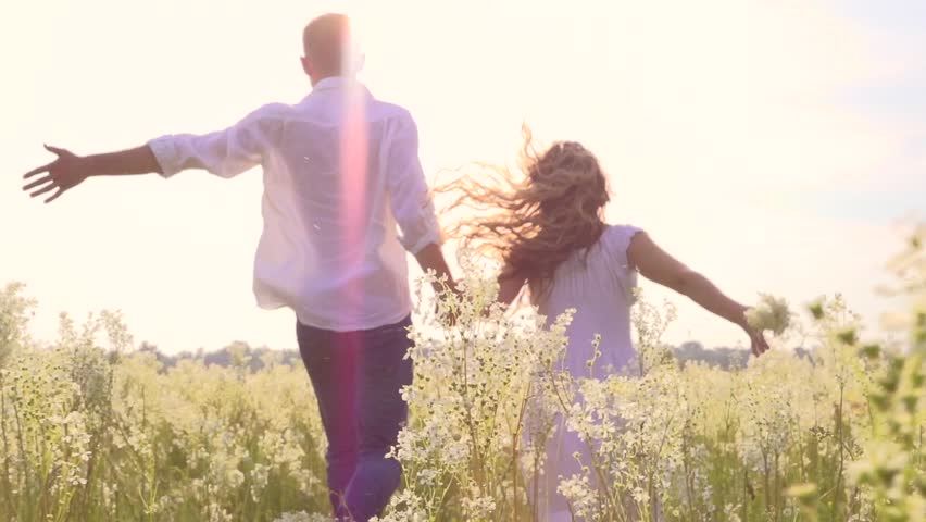 Happy couple having fun outdoors. Couple running away being excited with the freedom of the countryside. Young Man and woman holding hands and running through a field with wild flowers. Slow motion | Shutterstock HD Video #6462638