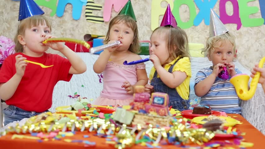 Five Little Kids Sit At Red Table With Cake And Blow In Multicolor Party  Blowers At