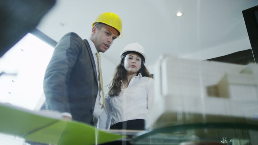 The development group of a project standing and discussing the office workers with model buildings and construction hats hd stock video clip malvernweather Choice Image