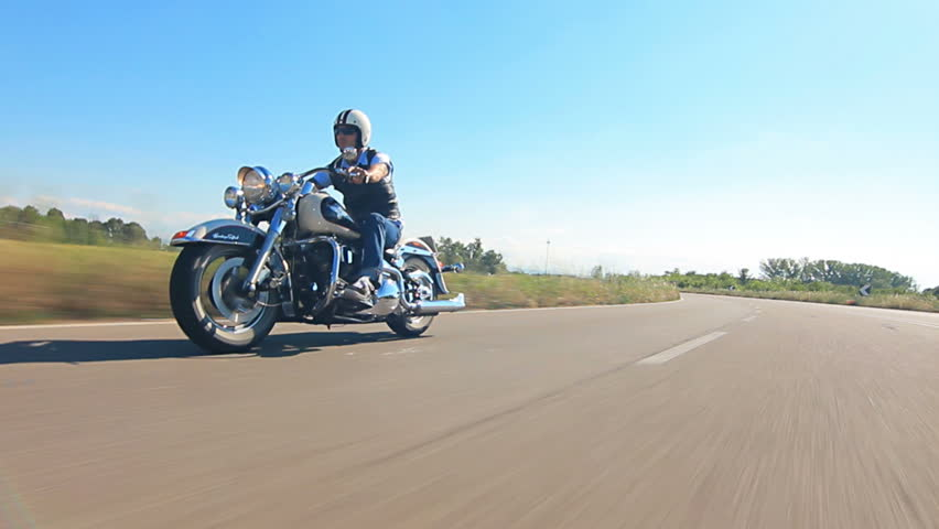 Man riding his motorcycle on a highway follofw shot car point of view
