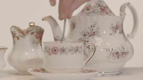 Afternoon tea - Close up of traditional vintage english bone china teapot pouring tea into teacup and saucer, milk jug adds milk, teaspoon adds sugar and stirs on plain white background.