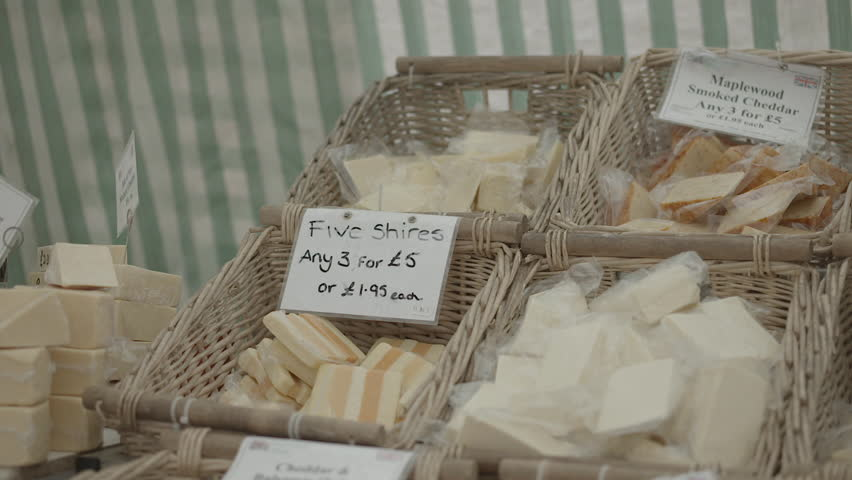 Close up of cheese stall baskets at farmers market including smoked cheddar and other organic cheeses for sale. Shot in Harrogate, England.