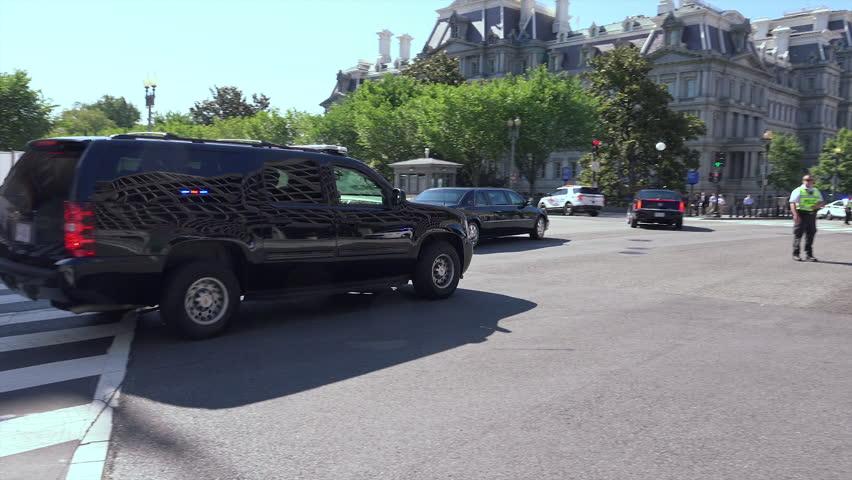 WASHINGTON, DC - JUNE 4, 2014: Small motorcade enters restricted Pennsylvania Ave heading toward White House.  Eisenhower Executive Office Bldg in b.g. 1 of 4 possible vehicle entrances to White House