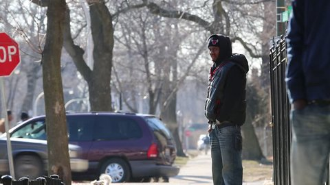 Chicago, Circa 2013: A Young African/American male wearing a hoodie sweatshirt stands on a street corner in Chicago, Circa 2013 Street corner activity in a high crime area