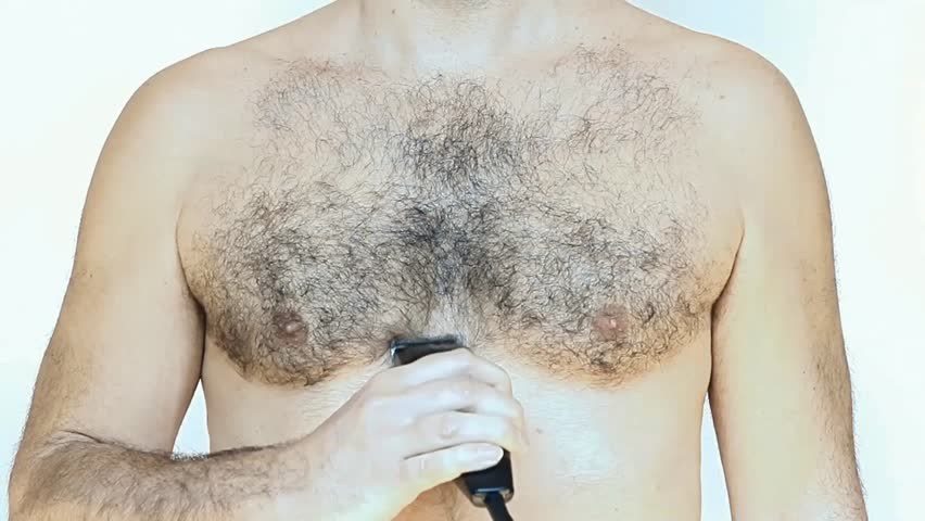 Man shaves his chest with an electric shaver on white background