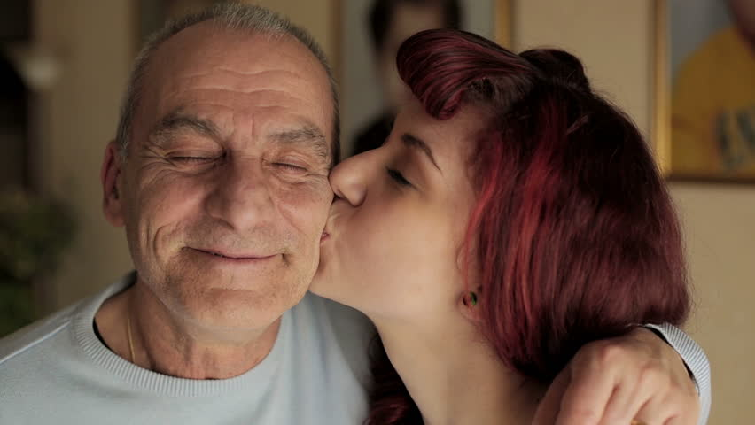Senior man and young girl smiling together. video filmed in close-up