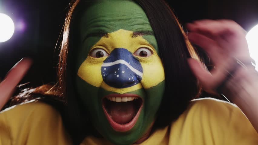 Female brazil fan is happily surprised on black background (close up) | Shutterstock HD Video #6562778
