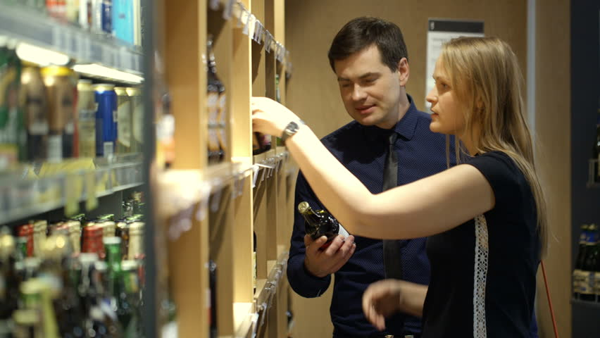 Man and woman choosing a bottle of wine in the shop. Woman checking prices