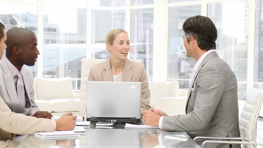 Smiling business people working at a computer in a meeting