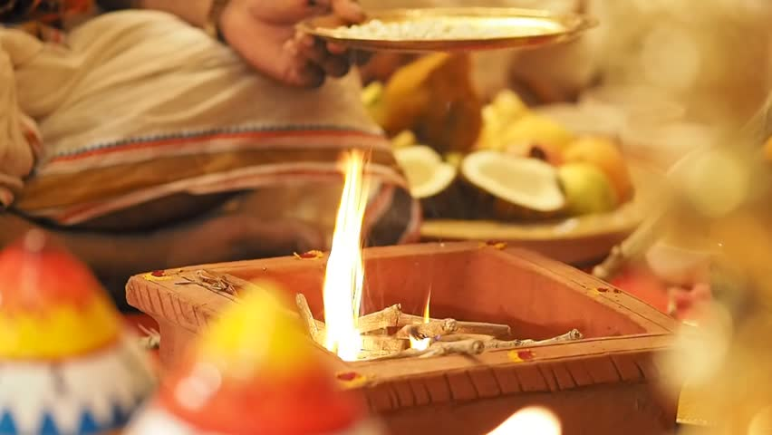 Oil and flowers is sacrificed to the sacred fire in a South Indian wedding ritual from Tamil Nadu