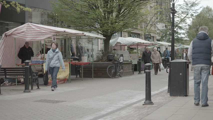 England - CIRCA 2014: Wide view of a local farmers market. People strolling along street browsing stalls. Filmed in Harrogate, North Yorkshire, UK.