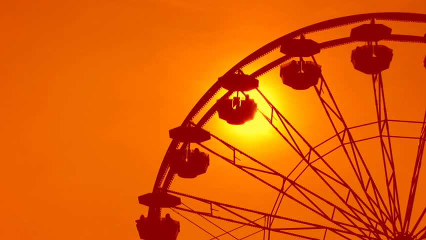 Ferris wheel detail. Dreamy orange sunset. Sky coloured orange, to simulate hot summer evening.