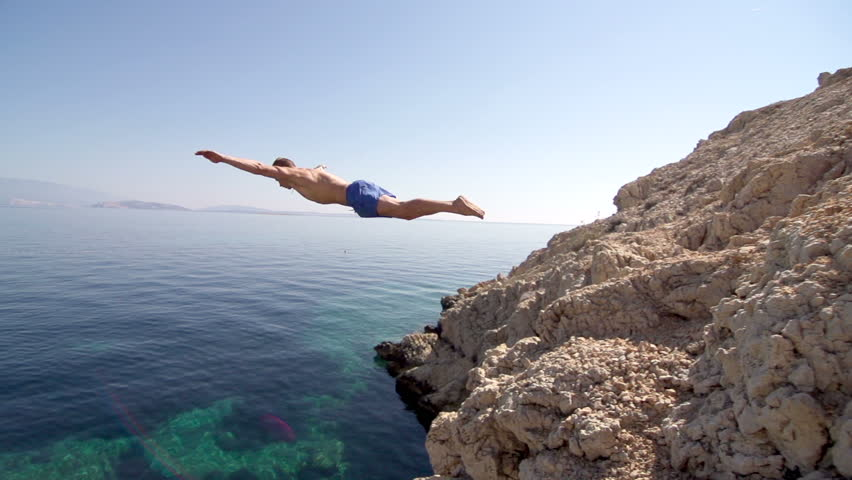 Slow Motion Of A Very Fit Man Jumping Of The Cliff Head First Into Clear Blue Water And Making A Splash. Sun Flares. | Shutterstock HD Video #6605894