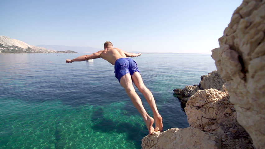 Beautiful Slow Motion Shot Of A Muscular Young Man Jumping Off The Cliff Into Clear Blue Water With Arms Outstretched. Sun Flares. #6613418