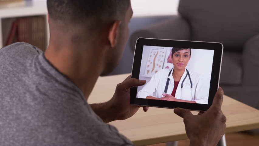 Black man listening to doctor on tablet