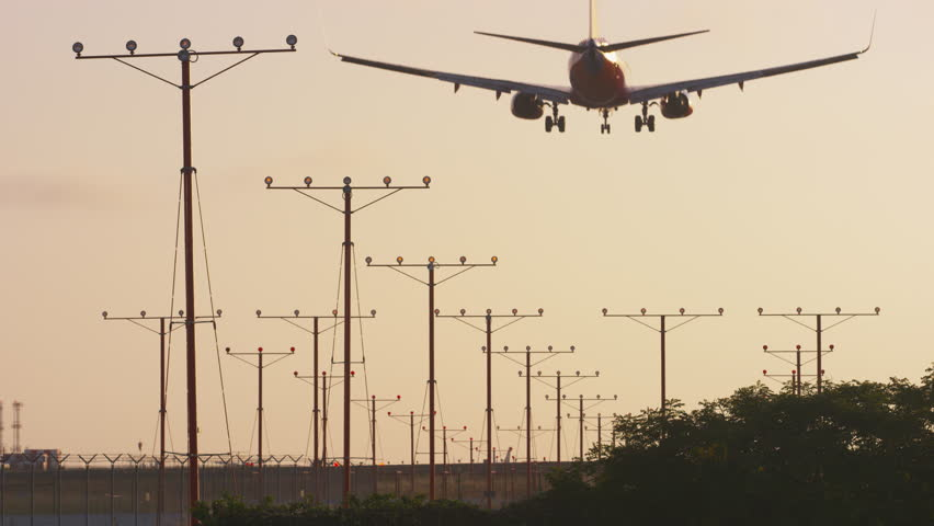Beautiful Plane Silhouette Lands on runway at sunset | Shutterstock HD Video #6636947