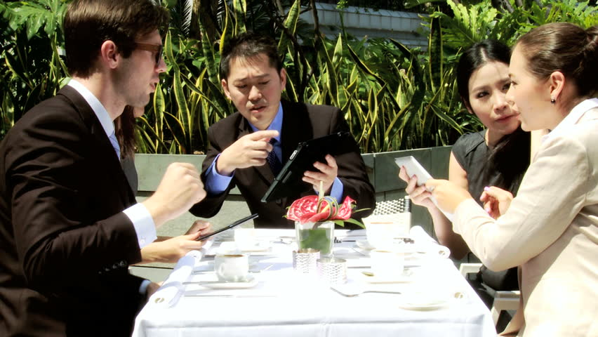 Male female Asian Chinese business partners meeting male Caucasian financial consultant wearing glasses wireless tablets over coffee outdoors office rooftop restaurant | Shutterstock HD Video #6646946