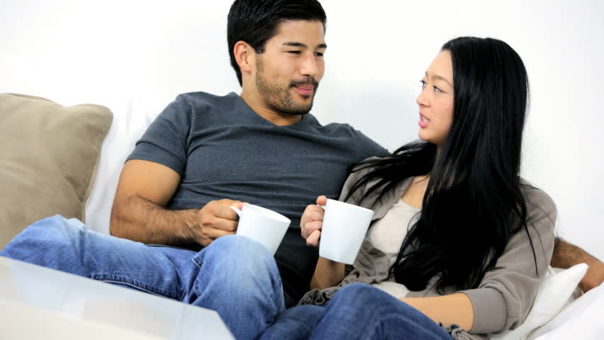 Happy Casually Dressed Young Asian Chinese Male Female Couple Enjoying Time  Together Talking Drinking Coffee Home Sofa Stock Footage Video 6655268 | ...
