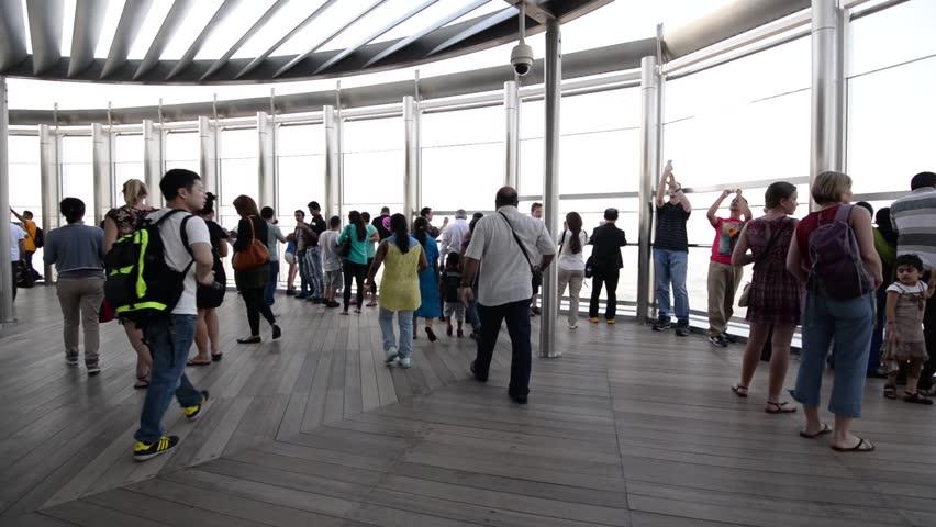 DUBAI, UAE - MARCH 30, 2014: People walking on Burj Khalifa observation terrace. Burj Khalifa is the tallest man-made structure in the world, at 829.8 m (2,722 ft).  | Shutterstock HD Video #6658991