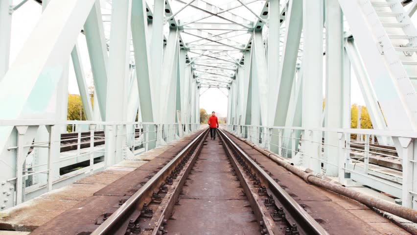 red-haired young man goes forward on camera on railway bridge